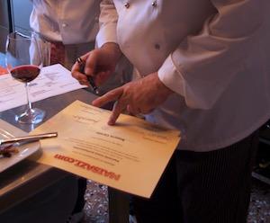 Lo chef Francesco mentre firma gli attestati alla fine di un corso per la ristorazione.