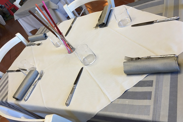Una tavola apparecchiata nella sala del Pastinaca Vegetarian Restaurant di Volterra, in Toscana.